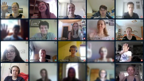 The photo shows a screenshot from a video conference. All participants have the webcam on. Some are waving at the camera. Both the Summer University team and the prospective students can be seen.