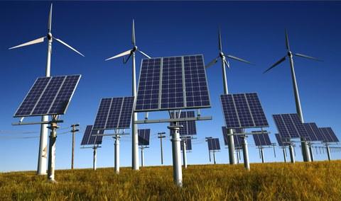 Das Foto zeigt im Vordergrund mehrere Solaranlagen und im Hintergrund mehrere Windräder.
