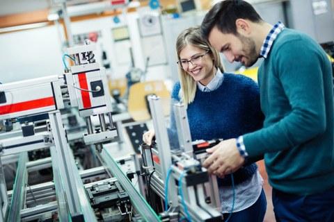 Das Foto zeigt zwei Studierende, die an einer hochtechnisierten Maschine stehen. Die Studierenden lächeln.