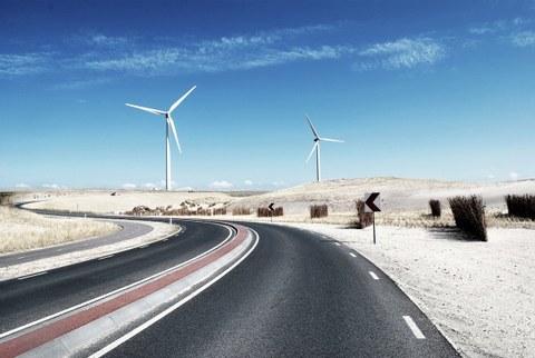 Das Foto zeigt eine Straße, die sich durch eine Wüstenlandschaft schlängelt. Im Hintergrund erkennt man zwei Windräder.