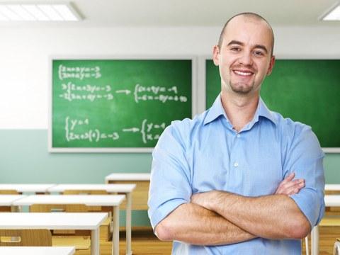 Das Foto zeigt einen Lehrer in seinem leeren Klassenraum. Er hat die Arme vor dem Körper verschränkt und lächelt in die Kamera.