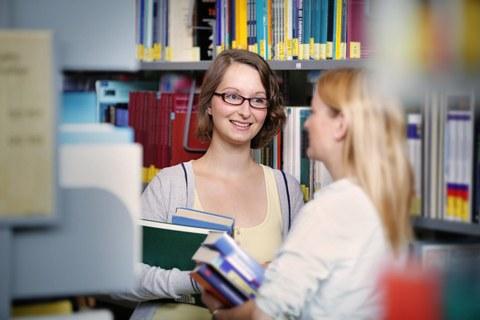 Das Foto zeigt zwei Studentinnen in der Bibliothek. Beide halten einige Bücher in den Händen und reden miteinander.
