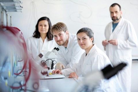 Das Foto zeigt vier Personen in Laborkitteln an einem Tisch. Auf dem Tisch steht ein Mikroskop. Die Personen schauen alle in die Kamera.