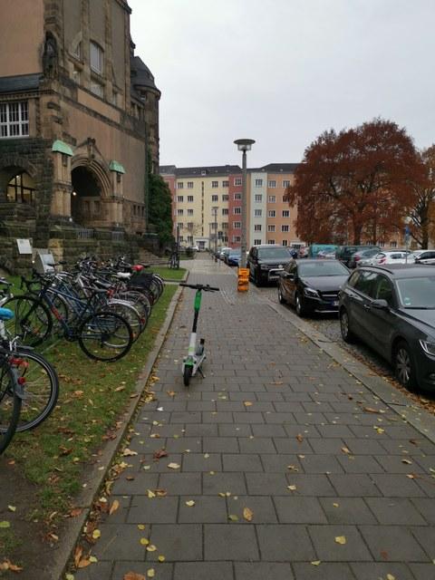 Abgestellter E-Scooter auf dem Fußweg vor dem Schumann-Bau