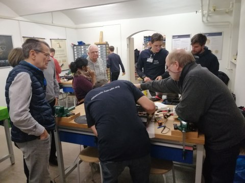 You can see several people in a room watching one person repair an old turntable.