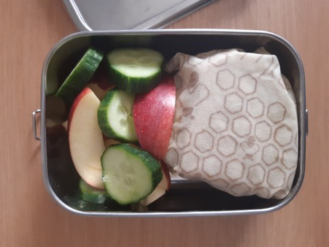 Lunchbox with sandwich wrap up in beewax wraps ad slices of apples and cucumber