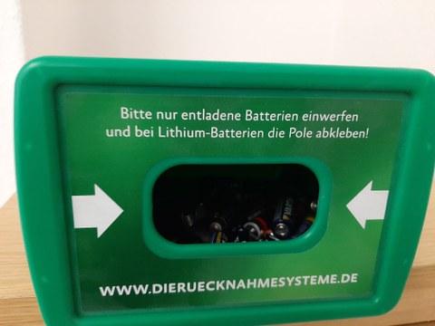 """Der Einwurf eines Batteriesammelkästchens mit Beschriftung: """"Bitte nur entladene Batterien einwerfen und beiLithium-Ion-Batterien die Pole abkleben!"""""""