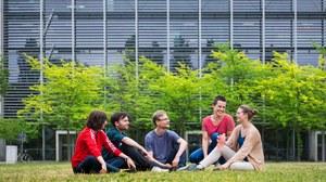 Foto einer Gruppe Studierender, die auf einer Wiese sitzen und sich unterhalten