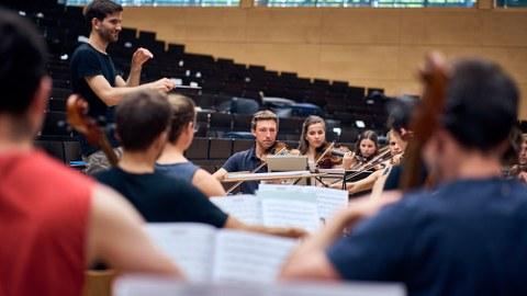 Foto einer Orchesterprobe des Universitätsorchester in einem Hörsaal