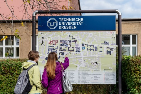 Photo of two women standing in front of a map of the TUD campus and pointing to it
