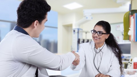 A doctor with a stethoscope handshaking with a patient