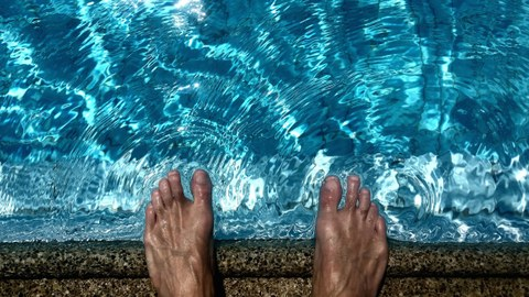 Feet which stand next to a swimming pool