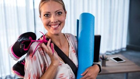 lächelnde Frau mit Sportmatte und -schuhe in den Händen