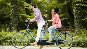 zwei Menschen fahren auf einem Tandemfahrrad