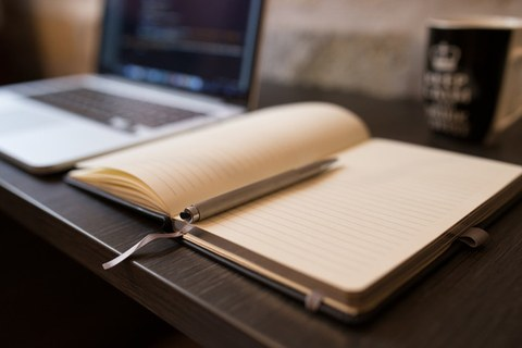In the front are an open notebook with empty pages and a pen. In the background is a laptop.