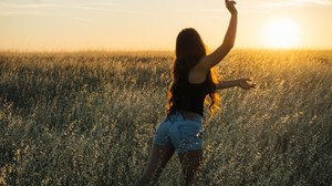 An energized woman in a field at sunset