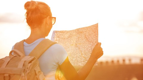 Woman with a backpack and a hiking map