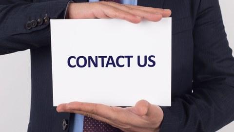 """Hände, die ein Schild mit der Aufschrift """"Contact us"""" halten"""
