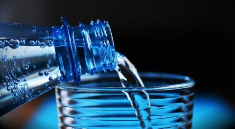 Aus einer Glasflasche wird Wasser in ein Glas gefüllt.