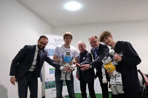 Die fünf genannten Herren stehen nebeneinander, etwas vorgebeugt, und strecken jeweils eine Hand aus.  Hr. Gemkow hält einen kleinen Fußball in der Hand,  Hr. Jagla und Hr. Loos halten jeweils einen kleinen Roboter.
