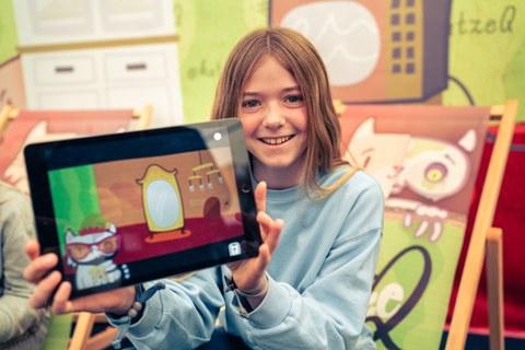 Ein Mädchen zeigt ein Tablet, in dem die App Katze Q zu sehen ist.