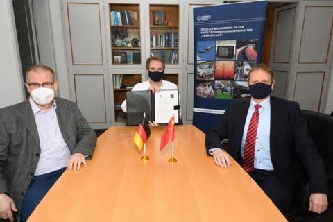 Drei Herren mit Maske sitzen an einem hellbraunen Tisch. Der Herr in der MItte hält eine Mappe in der Hand.
