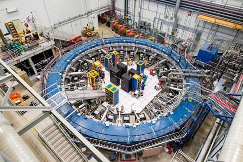 Blick auf den blauen Muon g-2 Ring, er befindet sich in seiner Detektorhalle inmitten von Elektronikregalen, der Myonen-Beamline und anderen Geräten.