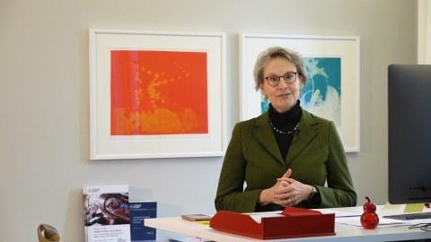 Fotoaufnahme einer Frau, die hinter einem Schreibtisch steht.