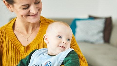 Links sitzt eine lächelnde Frau, auf deren Schoß sitzt ein Baby.