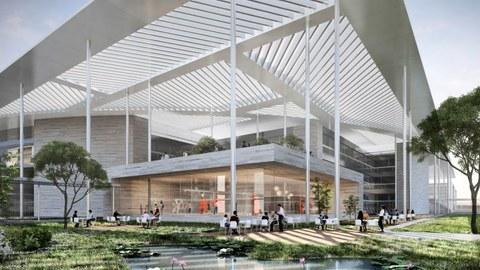 Blick auf dein würfelförmiges Gebäude, vor dem an weißen Tischen auf weißen Stühlen Menschen sitzen. Vor dem GEbäude befindet sich ein Teich. Das Gebäude ist von einem dreieckigen Glasdach überdacht.