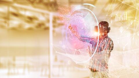Ein junger Mann mit 3D-Brille steht dem Betrachter zugewandt hinter einem Hologramm mit der schematischen Darstellung eines Netzwerkes.ra
