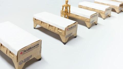 Auf dem Foto sind fünf, nebeneinander schräg von links unten nach rechts oben aufgestellte, Feldbetten aus Pappe zu sehen, neben dem 2. Bett von links steht eine Puppe.