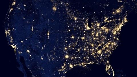 Blick aus dem Weltraum auf die USA bei Nacht, Lichter sind zu erkennen.