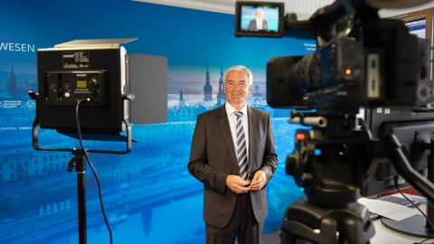 Prof. Dr. Jürgen Stamm führt durch die Online-Veranstaltung, rechts im Vordergrund ein Monitor, links eine Kamera, hinter Prof. Stamm ein blauer Hintergrund.