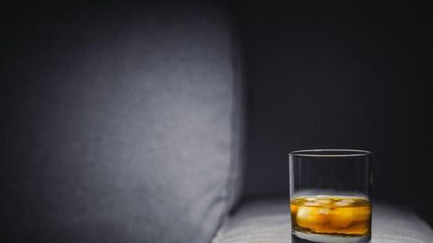 Foto von einem Glas Whiskey mit Eis, das auf einer grauen Sofalehne steht.