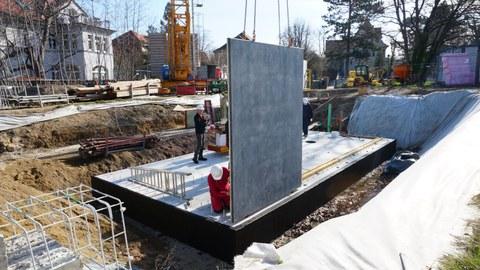 Baustelle, auf eine Bodenplatte wird eine senkrechte Betonscheibe aufgebracht.