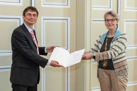 Prof. Friedrich (links) und Prof. Staudinger bei der Übergabe einer Urkunde, beide blicken in die Kamera.
