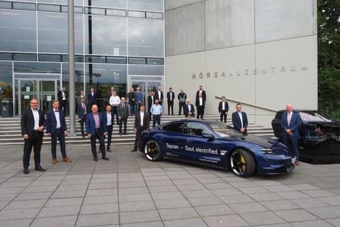 Vertreter der Porsche AG und der TU Dresden sowie Gästemit Porsche Taycan (vorn li.) inklusive Schnellladesystem sowie Cockpit