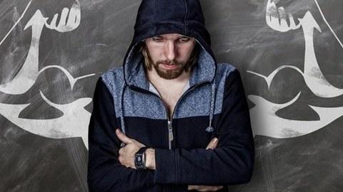 Mann mit Bart steht vor einem Wandbild, das muskulöse Arme darstellt