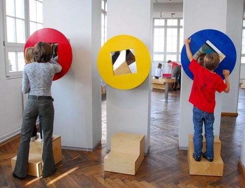 Zwei Kinder experimentieren mit großen roten und blauen Scheiben