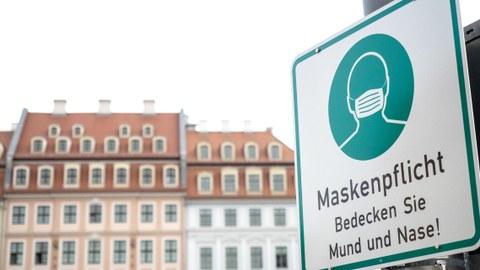 Vor dem Hintergrund einer Altbaufassade steht rechts ein Schild, das auf Maskenpflicht hinweist.