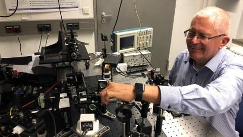Prof. Czarske im Labor, er bedient mit der rechten Hand eine Versuchsanordnung.