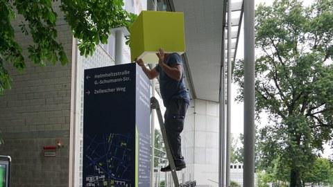 Eine Person steht auf einer Leiter vor dem Hörsaalzentrum und montiert einen hellgrünen Würfel auf den dunkelblauen Wegweiser.