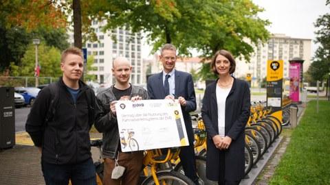 Vier Personen stehen im Halbkreis vor einer Reihe gelber Fahrräder. Die zweite Person von links hält einen symbolischen Vertrag in der Hand.
