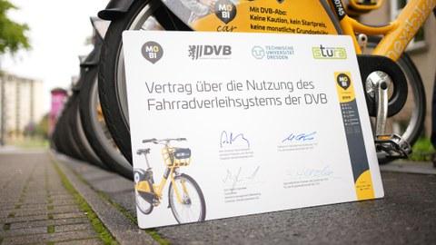 Symbolischer Vertrag zwischen TUD und DVB vor einer Reihe gelber Fahrräder.