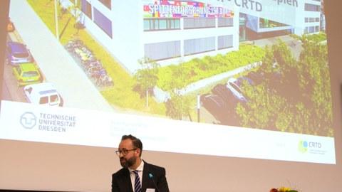 Wissenschaftsminister Sebastian Gemkow zur CRTD Feierstunde, im Hintergrund ein Foto des crtd-Gebäudes