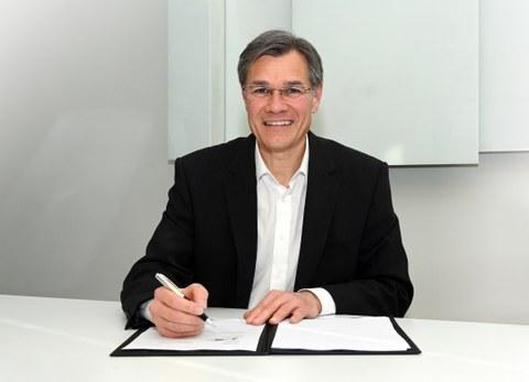 Porträtfoto Dr. Lamprecht vor einer geöffneten Unterschriftsmappe, in der rechten Hand hält er ein Schreibgerät.