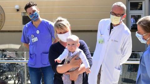Eine blonde Frau mit Mundschutz hält ein Baby auf dem Arm, sie wird umringt von Pflegepersonal