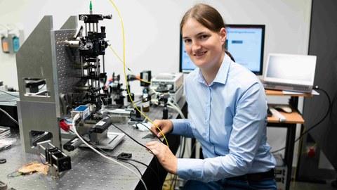 Frau Dr. Katrin Philipp sitzt rechts im Bild vor ihrem Mikroskop