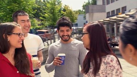 Junge Menschen verschiedener Nationalitäten trinken gemeinsam einen Kaffee auf dem Campus